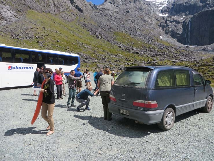Tourists taking pictures of a kea next to our campervan